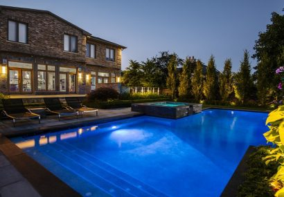 Backyard with lights on in swimming pool