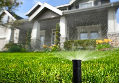 Sprinkler head watering front yard of house