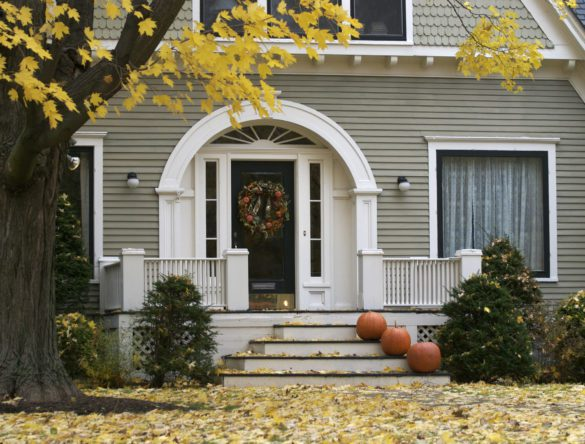 Suburban house prepared for fall with leaves falling around